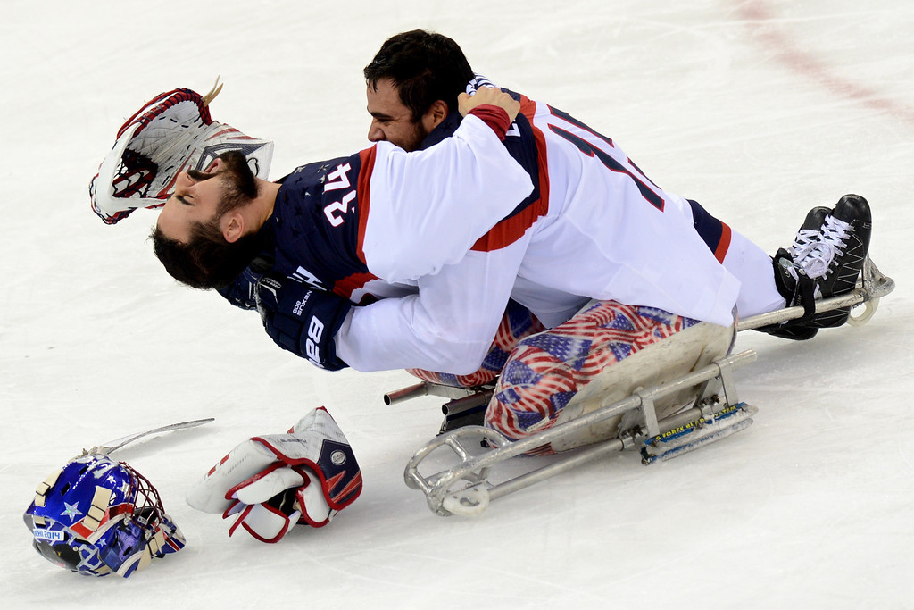. United States\' goalie Steve Cash (L) and Nikko Landeros celebrate their team\'s  victory in the Sledge Hockey Final match against Russia  at XI Paralympic Olympic games in the Shayba stadium near the city Sochi on March 15, 2014. USA won 1-0.  AFP PHOTO/KIRILL KUDRYAVTSEV/AFP/Getty Images