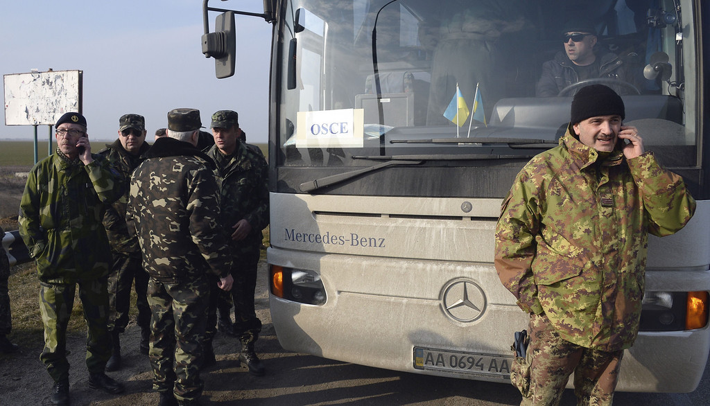 . OSCE military observers talk on the phone as they wait at the Chongar check point blocking the entrance to Crimea on March 7, 2014. Two buses carrying OSCE observers trying to enter Crimea turned back Friday after being blocked by armed men at a checkpoint, an AFP reporter said. Two sources within the mission said the team of 47 military and civilian observers was returning to the Ukrainian city of Kherson where they had spent the night after being similarly blocked on Thursday. ALEXANDER NEMENOV/AFP/Getty Images