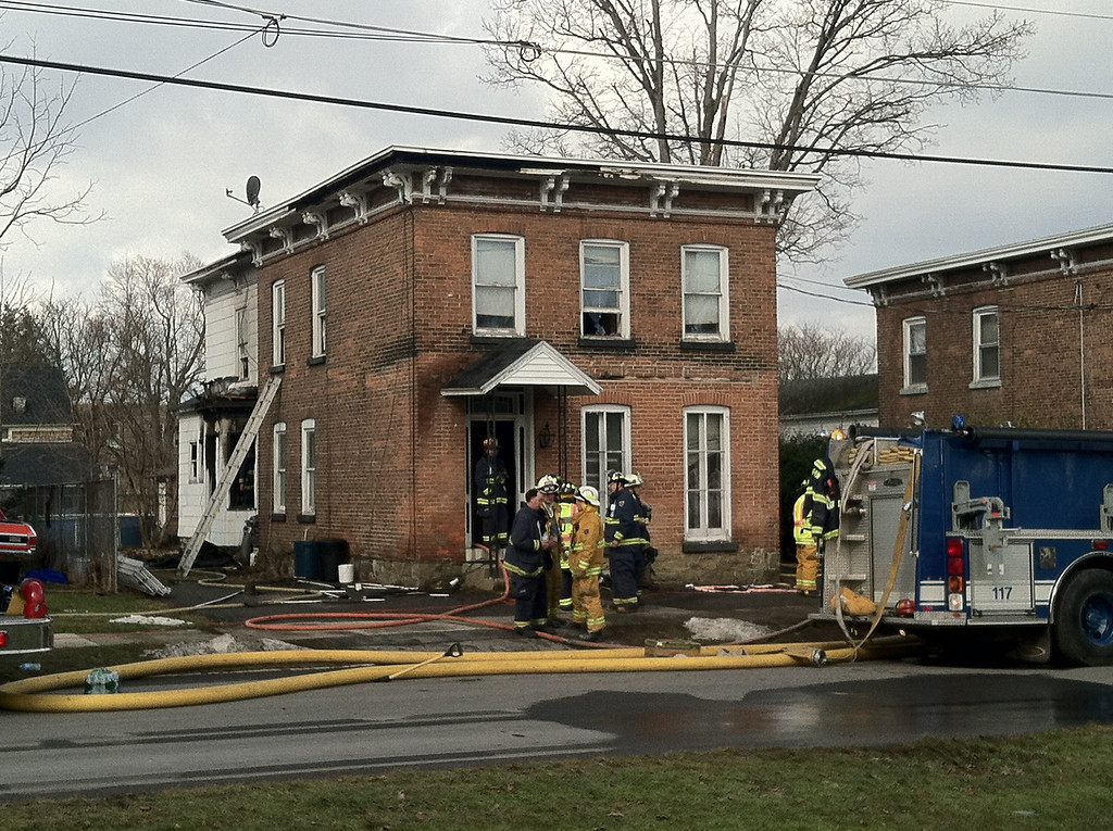. Firefighters battle a structure fire at an apartment building at 32 S. Washington St. in the village of Mohawk, N.Y., in connection with two shootings, Wednesday, March 13, 2013,  at two different businesses that left four people dead and at least two wounded, according to police.  State police told Mohawk Valley local media outlets a man shot and killed two unidentified people Wednesday morning at Gaffeyís Fast Lube in the village of Herkimer. Two others were killed at John\'s Barber Shop, a mile away in the village of Mohawk.  They said a total of six people had been shot.  (AP Photo/Observer-Dispatch, Steve Hughes)