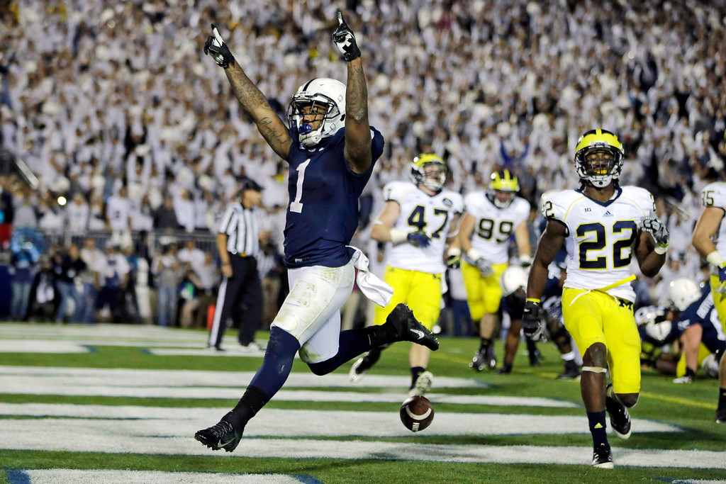 . Penn State running back Bill Belton (1) runs a two-yard touchdown as Michigan safety Jarrod Wilson (22) tries to defend during the fourth overtime period in an NCAA college football game in State College, Pa., Saturday, Oct. 12, 2013. Penn State won 43-40. (AP Photo/Gene J. Puskar)