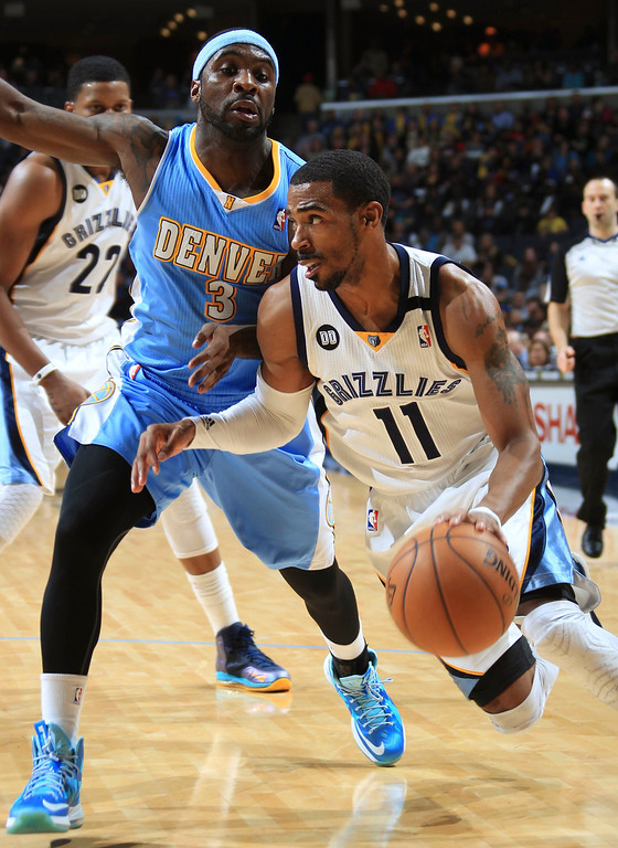 . Memphis Grizzlies guard Mike Conley (11) drives against the defense of Denver Nuggets guard Ty Lawson (3) during the first half of their NBA basketball game in Memphis, Tennessee December 29, 2012.  REUTERS/Nikki Boertman (UNITED STATES - Tags: SPORT BASKETBALL)