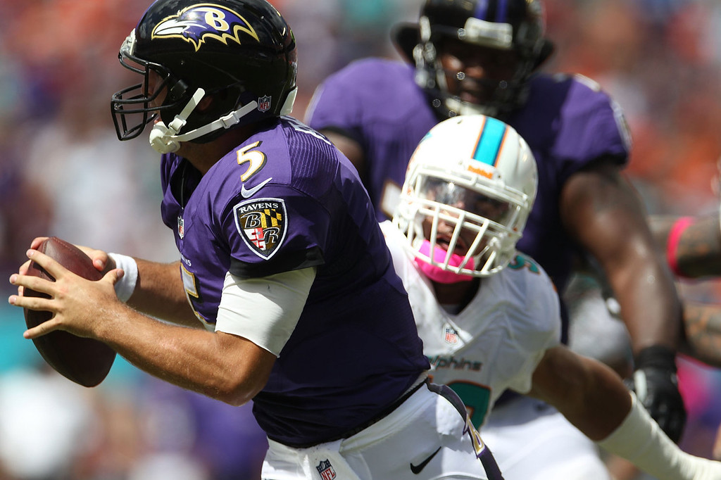 . Quarterback Joe Flacco #5 of the Baltimore Ravens is sacked by Linebacker Olivier Vernon #50 of the Miami Dolphins at Sun Life Stadium on October 6, 2013 in Miami Gardens, Florida.  (Photo by Marc Serota/Getty Images)