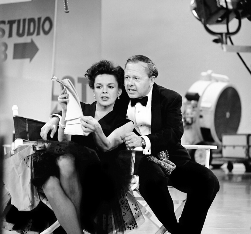 . In this June 26, 1963, file photo, Judy Garland and Mickey Rooney put their heads together over a television script for their first onstage reunion in 18 years, for the taping of the first of 32 variety shows which Garland will do for CBS next season. (AP Photo/File)
