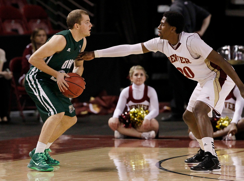 . Ohio guard Travis Wilkins, left, looks to pass the ball under pressure from Denver forward Royce O\'Neale in the first half of a first-round NIT college basketball game in Denver on Tuesday, March 19, 2013. (AP Photo/David Zalubowski)