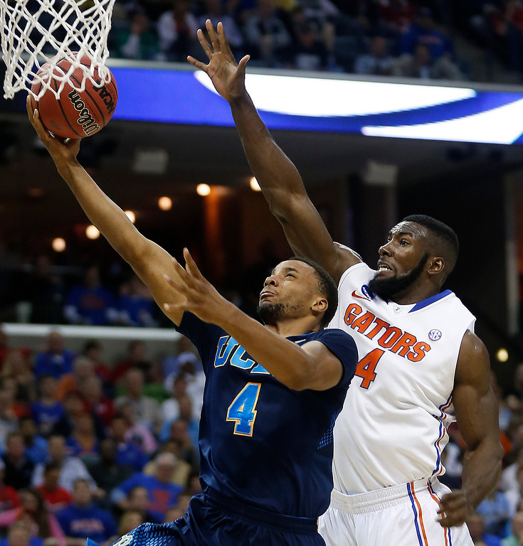 . UCLA guard Norman Powell (4) shoots against Florida center Patric Young (4) during the first half in a regional semifinal game at the NCAA college basketball tournament, Thursday, March 27, 2014, in Memphis, Tenn. (AP Photo/John Bazemore)