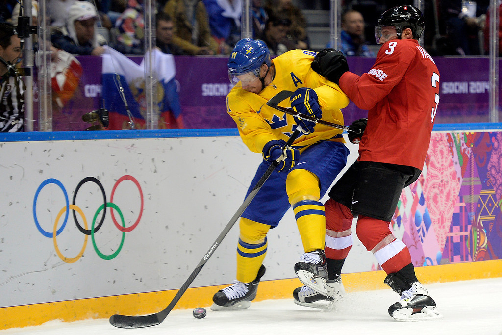 . Switzerland\'s Julien Vauclair defends Sweden\'s Daniel Alfredsson during the action at Bolshoy Arena. Sochi 2014 Winter Olympics on Friday, February 14, 2014. (Photo by AAron Ontiveroz/The Denver Post)