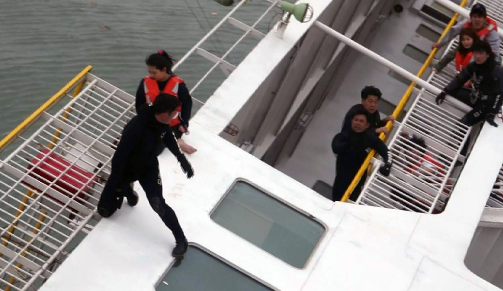 . This photo taken at sea some 20 kilometers off the island of Byungpoong in Jindo on April 16, 2014 shows South Korea Coast Guard members rescuing some of the 477 passengers and crew aboard a South Korean ferry capsizing on its way to Jeju island from Incheon. South Korea\'s coastguard said on April 16, it had recovered one body as it struggled to rescue 477 people -- mostly high school students -- from a capsized ferry off the southern coast.   AFP PHOTO/YONHAPYONHAP/AFP/Getty Images
