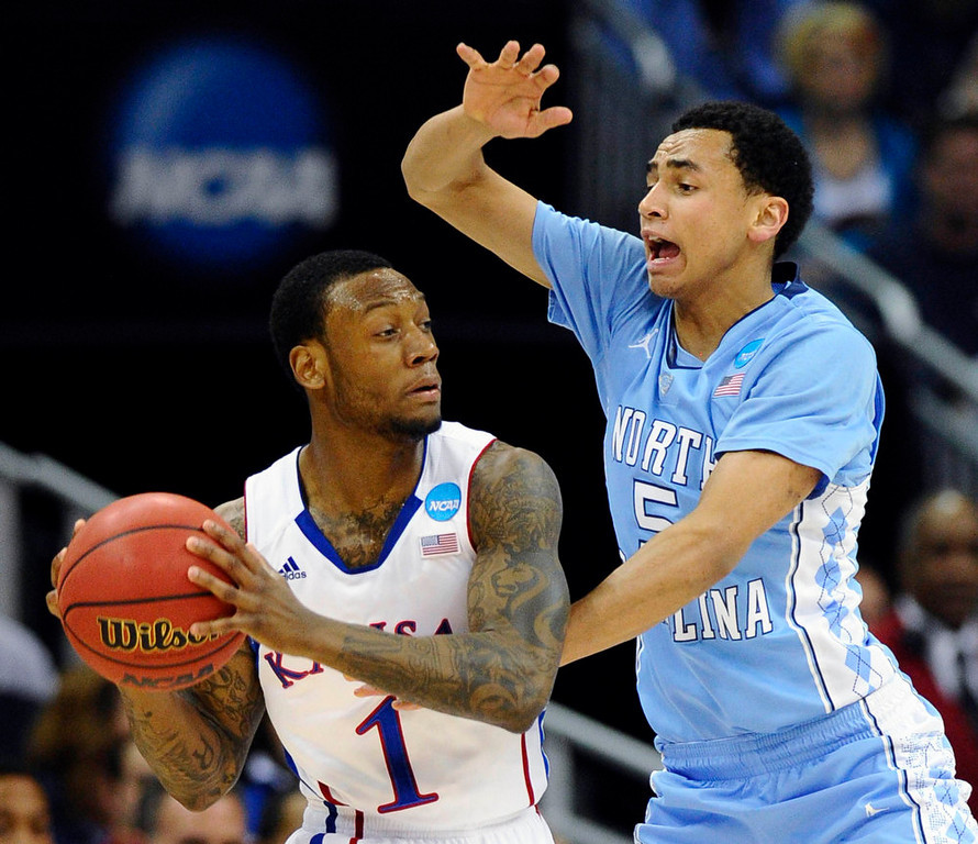 . North Carolina Tar Heels guard Marcus Paige (R) pressures Kansas Jayhawks guard Naadir Tharpe during the first half of the third round of the NCAA men\'s basketball tournament at the Sprint Center in Kansas City, Missouri March 24, 2013. REUTERS/Dave Kaup
