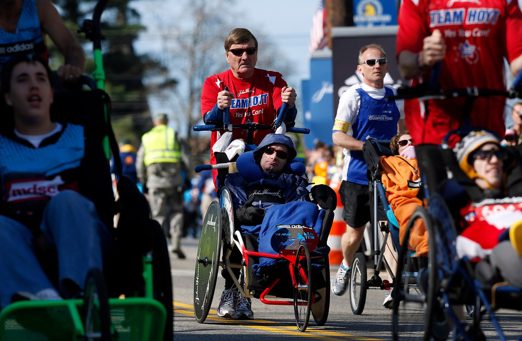 . Dick Hoyt pushes his son Rick Hoyt, both from Holland, Mass., center, as they compete in the wheelchair division of the 118th Boston Marathon Monday, April 21, 2014 in Hopkinton, Mass. They are competing in their 32nd Boston Marathon and have said this will be their last.  (AP Photo/Michael Dwyer)
