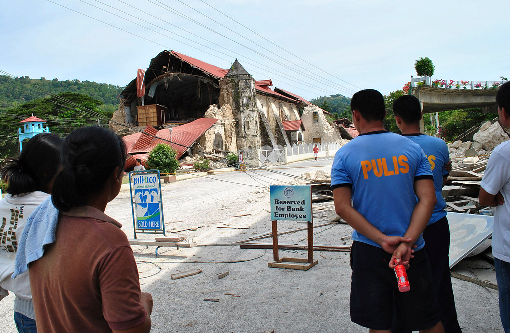 . Residents look at the remains of the Loboc Chruch following a 7.2-magnitude earthquake that hit Bohol, central Philippines, Tuesday, Oct. 15, 2013.  (AP Photo)