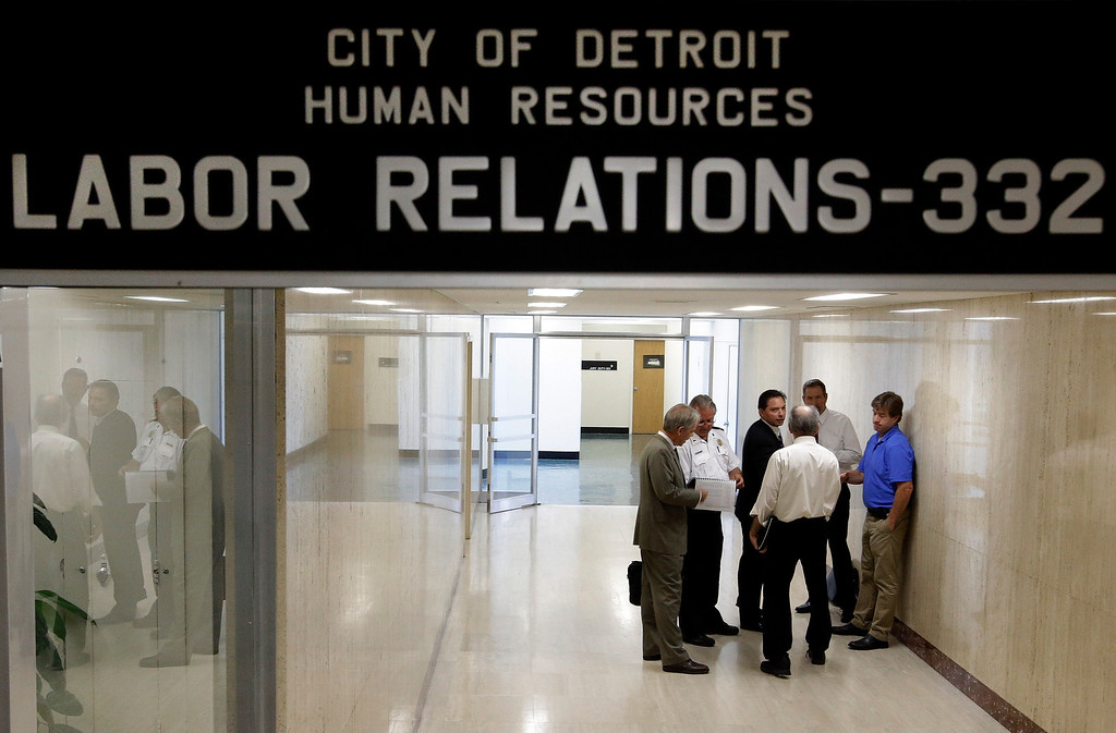 . Representatives of Detroit\'s active and retired public workers look at papers before a meeting in Detroit, Wednesday, July 10, 2013. Representatives of Detroit\'s active and retired public workers met behind closed doors Wednesday with the restructuring team of the city\'s state-appointed emergency manager, who is seeking huge cuts in pension benefits and health insurance to avoid the largest municipal bankruptcy in U.S. history. (AP Photo/Paul Sancya)