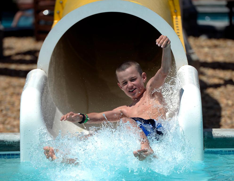 . Esten Dixon 9, rides down the slide at Pirates Cove July 16, 2013. (Photo By John Leyba/The Denver Post)