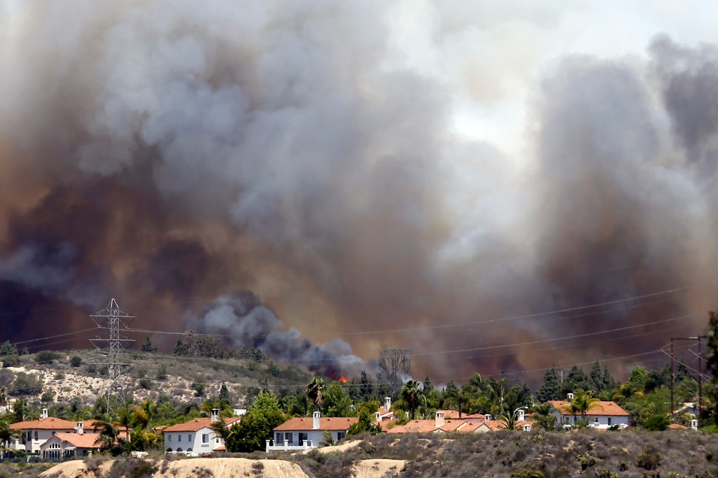 . Wildfire climbs a canyon toward homes Wednesday, May 14, 2014, in Carlsbad, Calif. More wildfires broke out Wednesday in San Diego County  threatening homes in Carlsbad and forcing the evacuations of military housing and an elementary school at Camp Pendleton as Southern California is in the grip of a heat wave. (AP Photo)