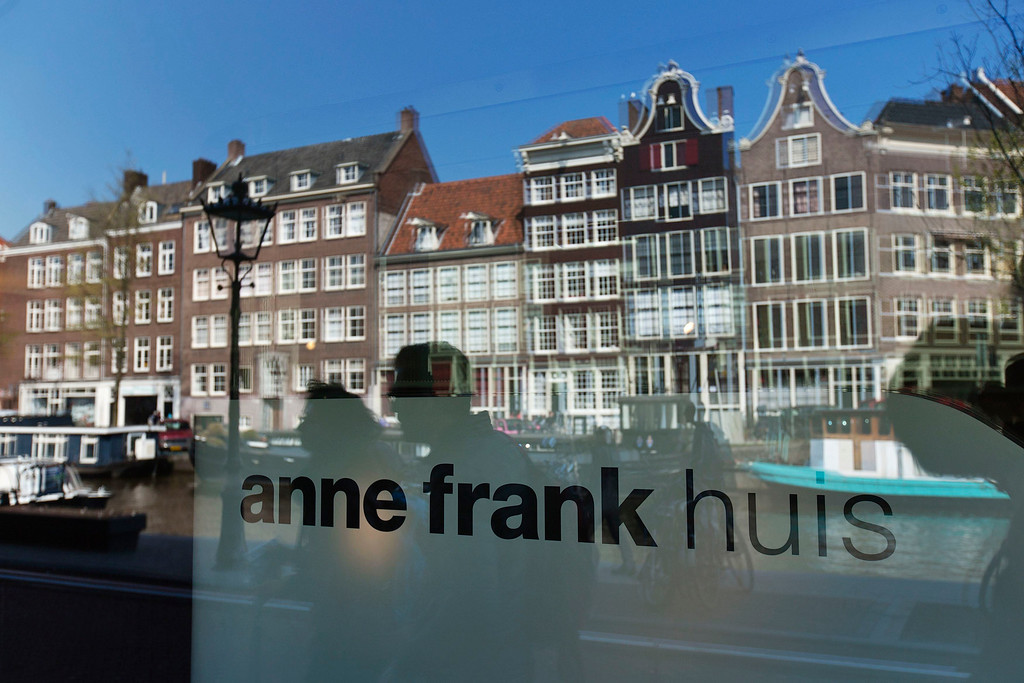 . Reflections of tourists and canal houses are seen in the window of the  Anne Frank museum in Amsterdam April 24, 2013. The Royal celebrations in the Netherlands this week put the country and the capital Amsterdam on front pages and television screens around the world with an orange splash. There\'s plenty to see and do in 48 hours in this compact city, where the world-famous Rijksmuseum only recently reopened after an extensive renovation. Picture taken April 24, 2013.  REUTERS/Michael Kooren