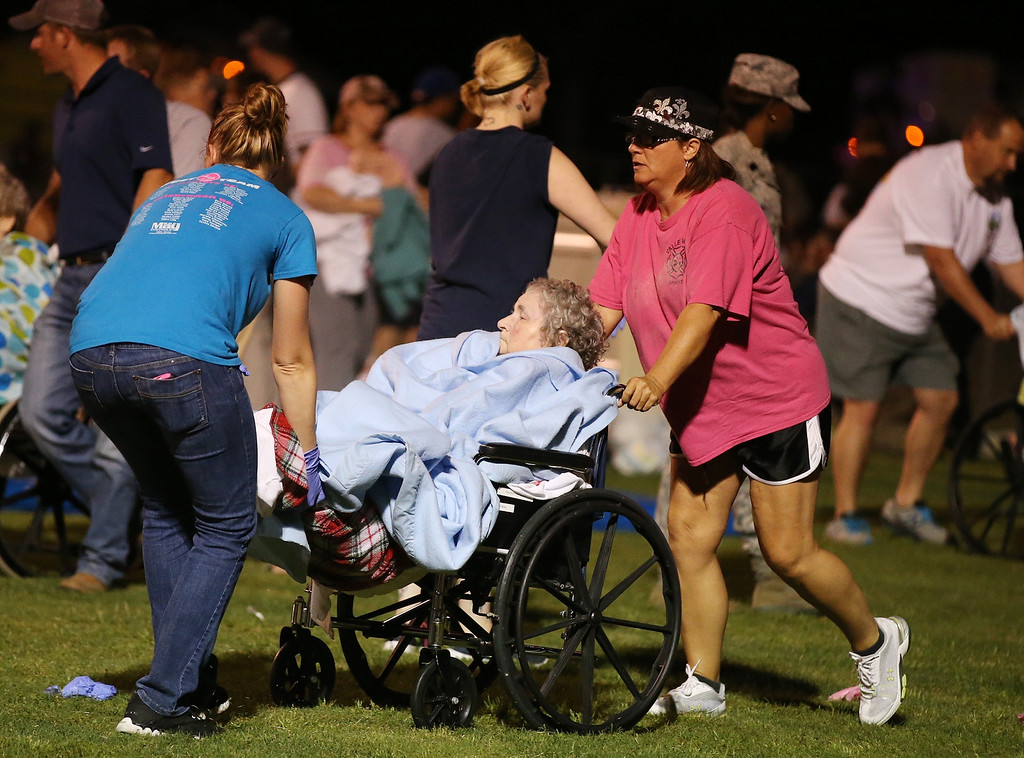 . An elderly person is assisted at a staging area at a local school stadium  following an explosion at a fertilizer plant Wednesday, April 17, 2013, in West, Texas. An explosion at a fertilizer plant near Waco caused numerous injuries and sent flames shooting high into the night sky on Wednesday. (AP Photo/ Waco Tribune Herald, Rod Aydelotte)