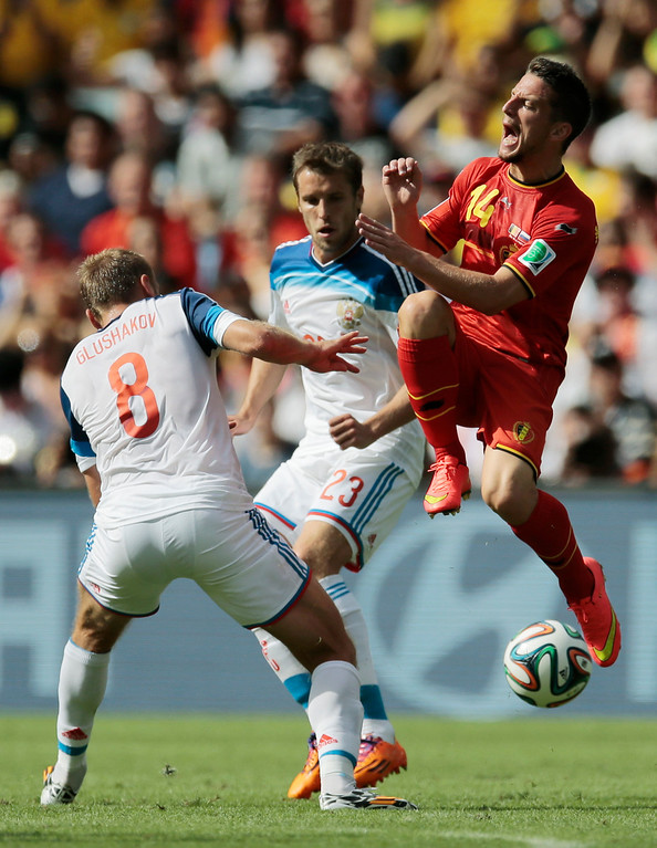 . Belgium\'s Dries Mertens, right, is challenged by Russia\'s Denis Glushakov, left, as Russia\'s Dmitry Kombarov, center, looks on, during the group H World Cup soccer match between Belgium and Russia at the Maracana stadium in Rio de Janeiro, Brazil, Sunday, June 22, 2014. (AP Photo/Ivan Sekretarev)