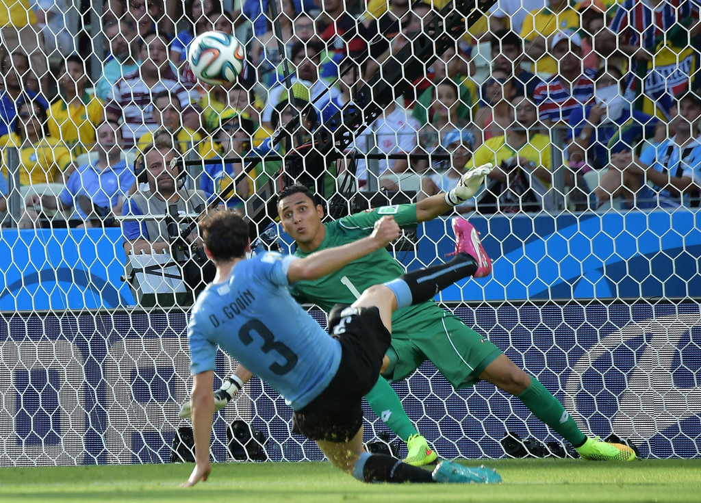 . Uruguay\'s defender Diego Godin (L) shoots the ball towards the goal of Costa Rica\'s goalkeeper Keylor Navas during a Group D football match between Uruguay and Costa Rica at the Castelao Stadium in Fortaleza during the 2014 FIFA World Cup on June 14, 2014. AFP PHOTO / GABRIEL BOUYS