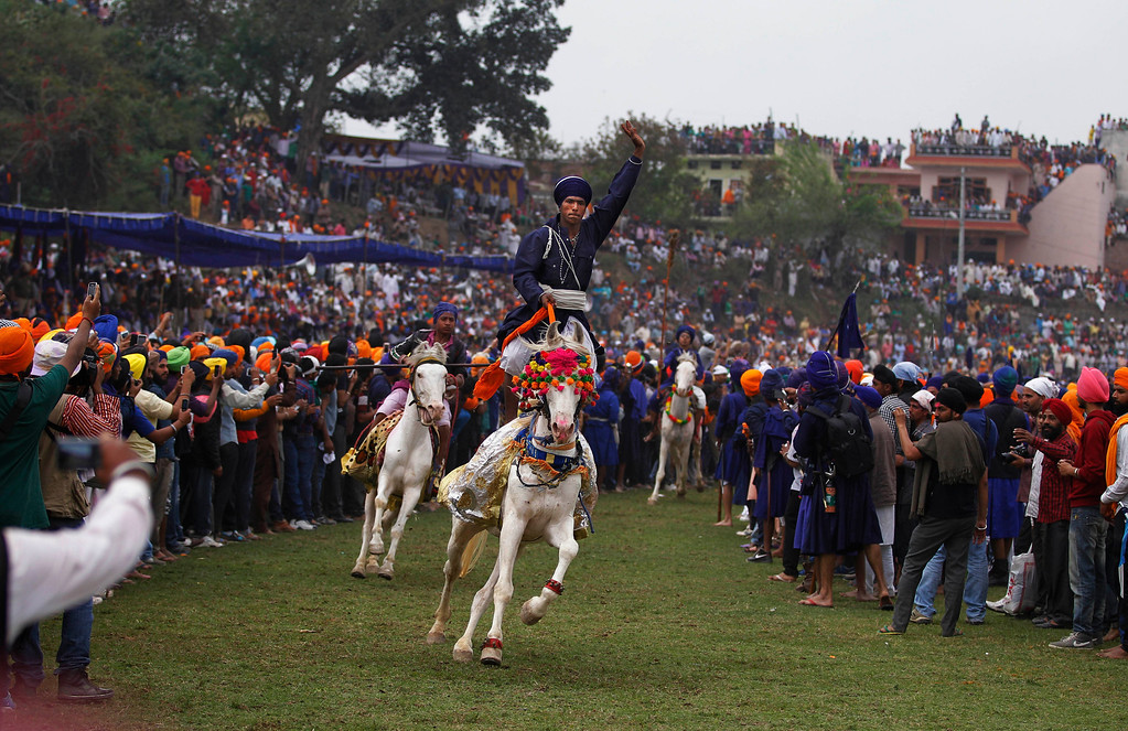 . People watch as Nihangs or Sikh warriors, display their horse riding skills during the annual fair of \'Hola Mohalla\'  in Anandpur Sahib, in the northern Indian state of Punjab, Monday, March 17, 2014. Believers from various parts of northern India collect at the religious fair to celebrate the festival of Holi in a tradition set by the tenth Sikh guru Guru Gobind Singh in the seventeenth century. Nihangs, or Sikh warriors, display their martial skills and attire during the fair, believed to be maintained in the exact tradition as set by the Guru. (AP Photo/Altaf Qadri)