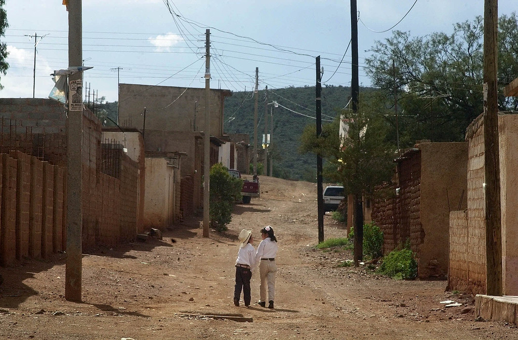 . Children hold hands while walking home from church in the border town of Los Pozos, Mexico, Sept. 2, 2001. (AP Photo/Gregory Bull)