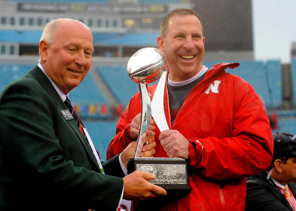 . Nebraska head coach Bo Pelini, right, and Gator Bowl Game Committee Chairman Andy Pradella, left, hold the trophy at the end of the Gator Bowl NCAA college football game against Georgia, Wednesday, Jan. 1, 2014, in Jacksonville, Fla. Nebraska won 24-19.  (AP Photo/Stephen B. Morton)
