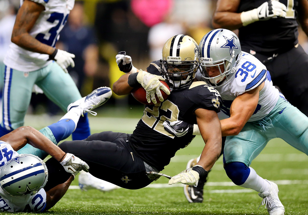 . Running back Mark Ingram #22 of the New Orleans Saints is tackled by strong safety Jeff Heath #38 of the Dallas Cowboys during a game at the Mercedes-Benz Superdome on November 10, 2013 in New Orleans, Louisiana.  (Photo by Ronald Martinez/Getty Images)