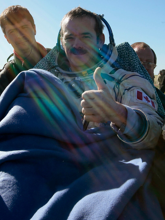. Ground personnel carry Canadian astronaut Chris Hadfield, as he gives a thumbs up, after the Russian Soyuz space capsule landed some 150 km (90 miles) southeast of the town of Zhezkazgan, in central Kazakhstan May 14, 2013. REUTERS/Mikhail Metzel/Pool