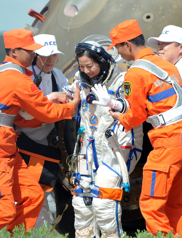 . Chinese female astronaut Wang Yaping (C) waves after getting out from the Shenzhou-10 spacecraft after it landed in the grasslands of north China\'s Inner Mongolia region on June 26, 2013, following a 15-day mission in space. China completed its longest manned space mission on June 26 as its Shenzhou-10 spacecraft and three crew members safely returned to Earth, in a major step towards Beijing\'s goal of building a permanent space station by 2020.  AFP PHOTOAFP/AFP/Getty Images