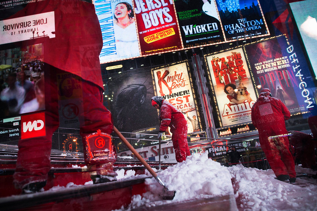 . Workers clean snow from the steps of TKTS Times Square ticket booth, Thursday, Jan. 2, 2014, in New York. The storm is expected to bring snow, stiff winds and punishing cold into the Northeast. (AP Photo/John Minchillo)