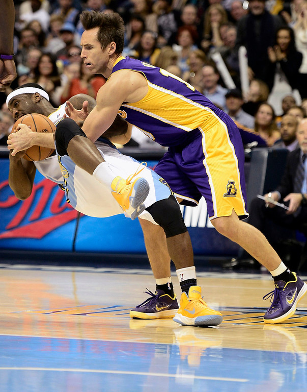 . Denver Nuggets\' Ty Lawson steals the ball from Los Angeles Lakers\' Steve Nash (R) during their NBA basketball game in Denver, Colorado February 25, 2013.   REUTERS/Mark Leffingwell