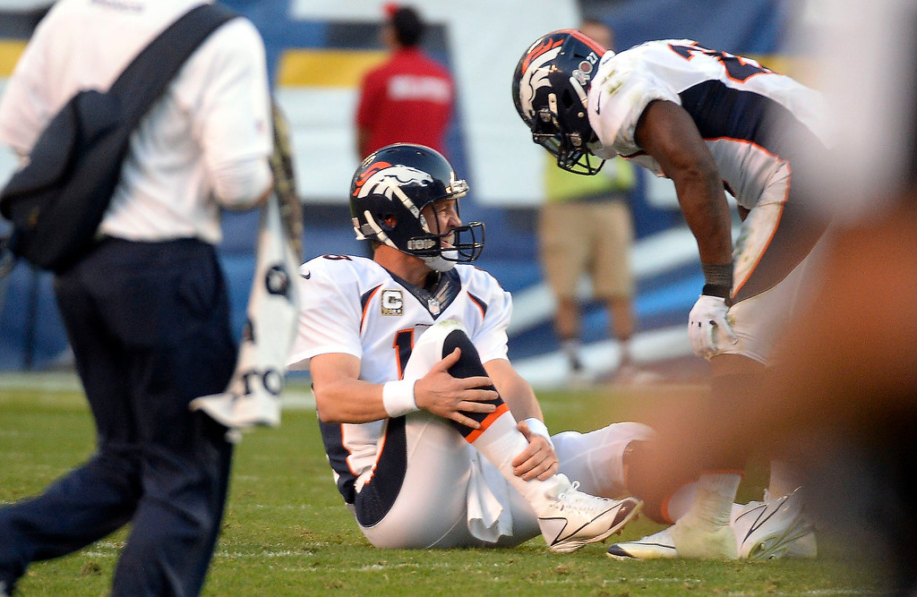 . Denver Broncos quarterback Peyton Manning (18) sits on the turf after going down grabbing his ankle in the fourth quarter against the San Diego Chargers at Qualcomm Stadium. (Photo by John Leyba/The Denver Post)