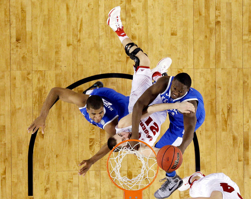. Wisconsin guard Josh Gasser is caught between Kentucky guard Aaron Harrison (2) and forward Julius Randle (30) during the first half of the NCAA Final Four tournament college basketball semifinal game Saturday, April 5, 2014, in Arlington, Texas. (AP Photo/David J. Phillip)