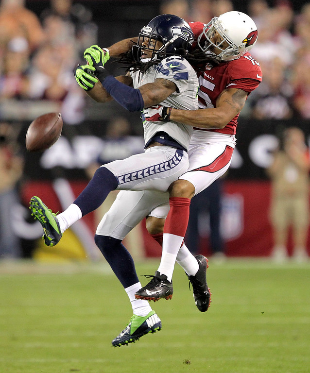 . Seattle Seahawks cornerback Richard Sherman (25) breaks up a pass intended for Arizona Cardinals wide receiver Michael Floyd during the first half of an NFL football game, Thursday, Oct. 17, 2013, in Glendale, Ariz. (AP Photo/Rick Scuteri)