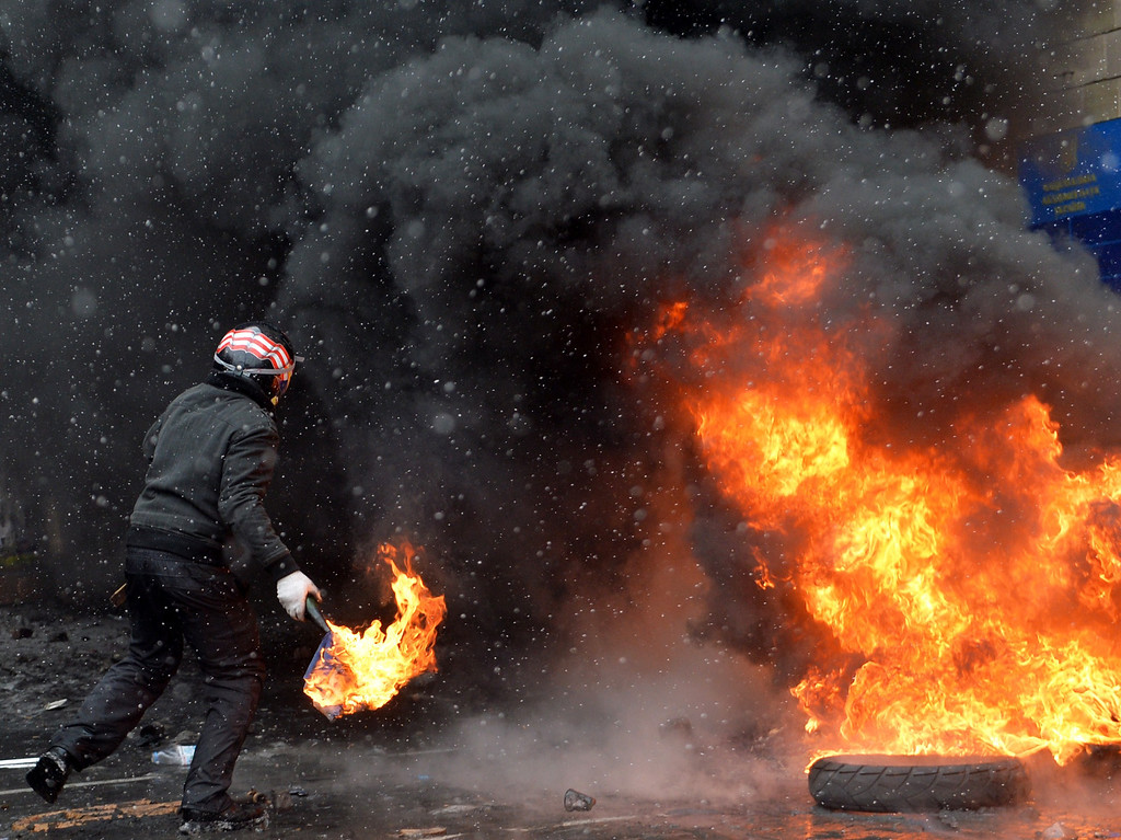 . A demonstrator throws an incendiary device as protestors clash with police in the center of Kiev on January 22, 2014.  AFP PHOTO / SERGEI  SUPINSKY/AFP/Getty Images