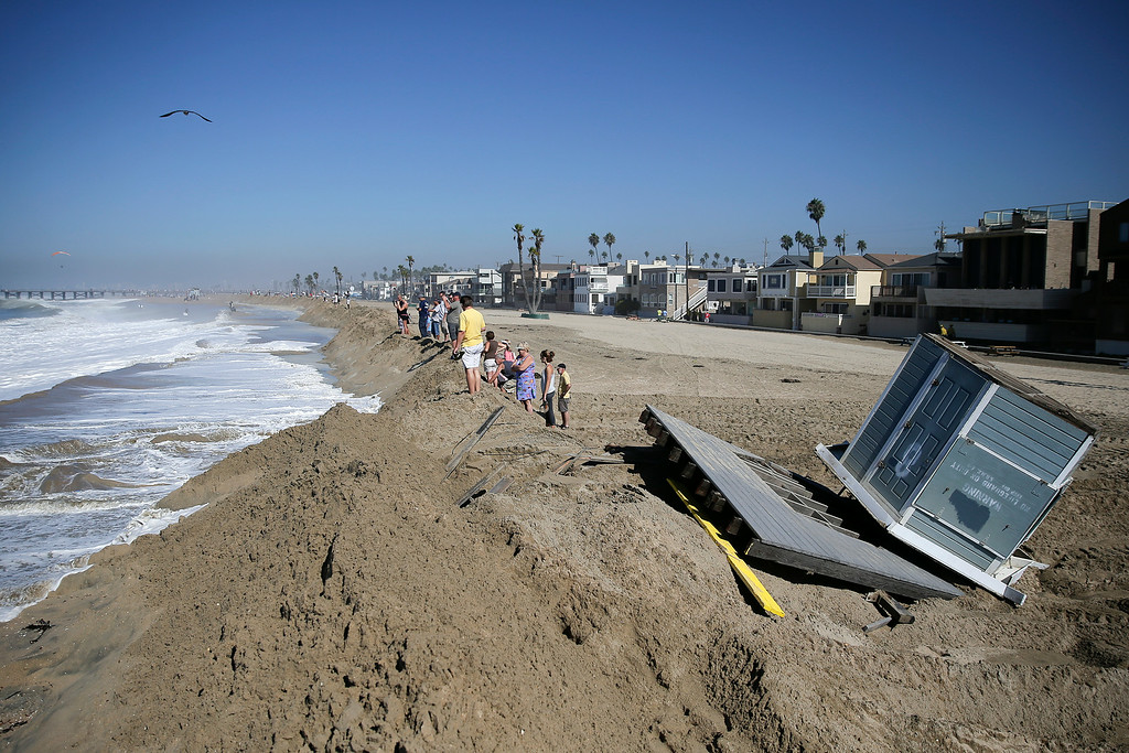. A lifeguard tower knocked over by high tides sits on the beach as people stand on the sand wall on Wednesday, Aug. 27, 2014, in Seal Beach, Calif. Parts of the low-lying Southern California coastal community of Seal Beach has been inundated by a surge of rising seawater brought on by Hurricane Marie spinning off Mexico\'s Pacific coast. (AP Photo/Jae C. Hong)