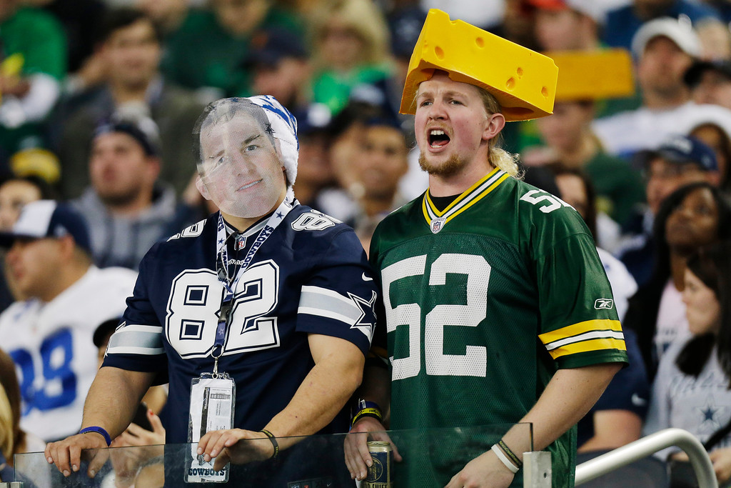. Dallas Cowboys and Green Bay Packers fans cheer during the first half of an NFL football game, Sunday, Dec. 15, 2013, in Arlington, Texas. (AP Photo/Tim Sharp)