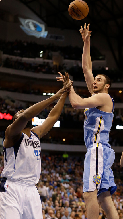 . Denver Nuggets center Timofey Mozgov, right, of Russia, shoots over Dallas Mavericks power forward Elton Brand (42) during the first half of an NBA basketball game on Friday, April 12, 2013, in Dallas. (AP Photo/LM Otero)