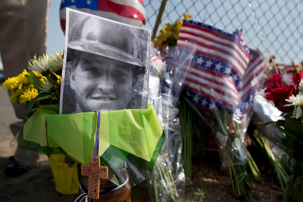 . A photo of one of the 19 Granite Mountain Hot Shot crew members who was killed fighting a wild land fire near Yarnell, Ariz. on Sunday, sits at a makeshift memorial outside the crew\'s fire station, Monday, July 1, 2013 in Prescott, Ariz. (AP Photo/Julie Jacobson)