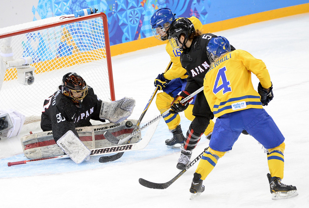 . Japan\'s goalkeeper Nana Fujimoto (L) saves the shot by Sweden\'s Jenni Asserholt (R) during the Women\'s Ice Hockey Group B match Sweden vs Japan at the Shayba Arena during the Sochi Winter Olympics on February 9, 2014.  ANDREJ ISAKOVIC/AFP/Getty Images