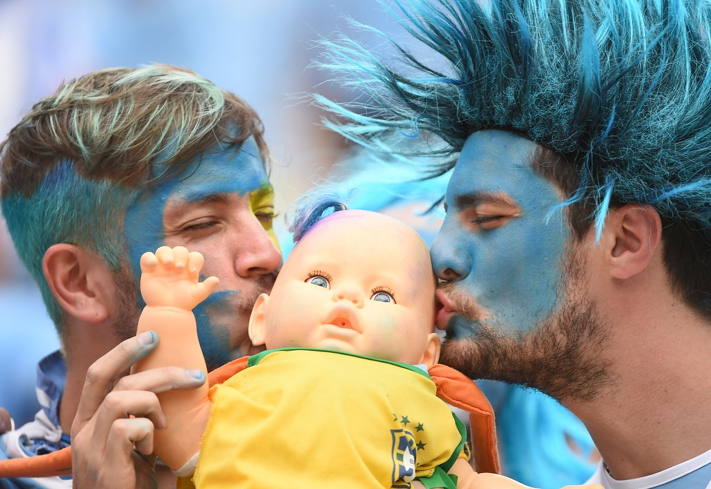 . Uruguay fans kiss a baby doll in a Brazil shirt prior to the Group D football match between Italy and Uruguay at the Dunas Arena in Natal during the 2014 FIFA World Cup on June 24, 2014. AFP PHOTO / EMMANUEL  DUNAND/AFP/Getty Images