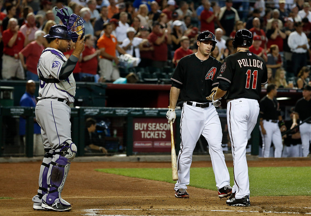 . Arizona Diamondbacks\' A.J. Pollock (11) celebrates his home run with teammate Paul Goldschmidt as Colorado Rockies\' Wilin Rosario, left, looks on in the first inning during a baseball game, on Saturday, April 27, 2013, in Phoenix. AP Photo/Ross D. Franklin)