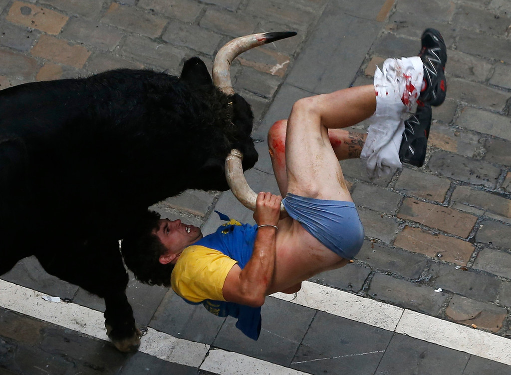. A runner gets gored by a bull on Estafeta street during the sixth running of the bulls of the San Fermin festival in Pamplona July 12, 2013. Four runners were gored in a run that lasted four minutes and fifty seven seconds, according to local media. REUTERS/Susana Vera