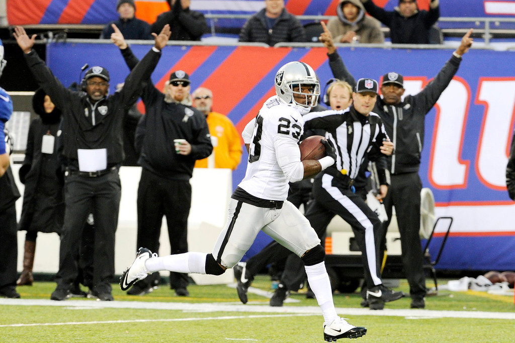 . Oakland Raiders cornerback Tracy Porter (23) runs in a touchdown after intercepting a pass from New York Giants quarterback Eli Manning during the first half of an NFL football game on Sunday, Nov. 10, 2013, in East Rutherford, N.J. (AP Photo/Bill Kostroun)