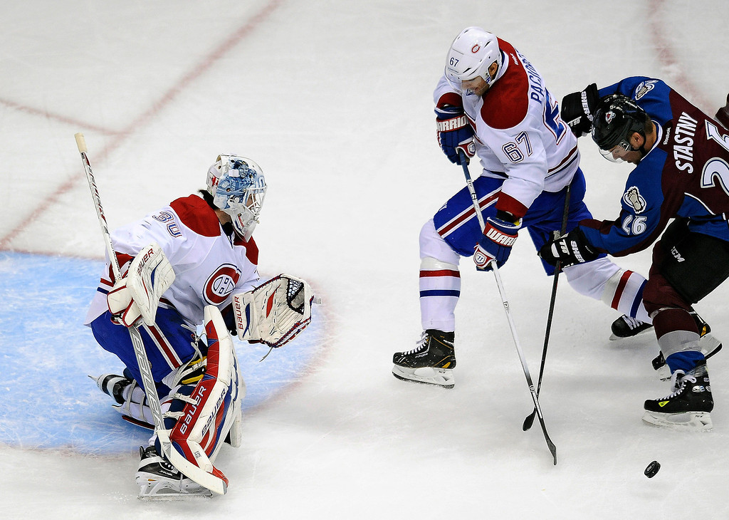 . Colorado Avalanche center Paul Stastny, right, and Montreal Canadiens left wing Max Pacioretty, center, fight for the puck in front of Canadiens goalie Peter Budaj, left, in the first period of an NHL hockey game on Saturday, Nov. 2, 2013, in Denver.  (AP Photo/Chris Schneider)