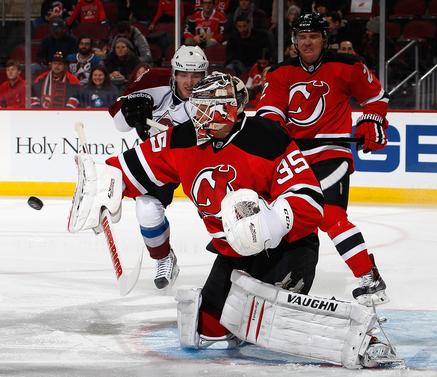 . Goalie Cory Schneider #35 of the New Jersey Devils makes a save as Matt Duchene #9 of the Colorado Avalanche skates in looking for the rebound during the first period of an NHL hockey game at Prudential Center on February 3, 2014 in Newark, New Jersey.  (Photo by Paul Bereswill/Getty Images)