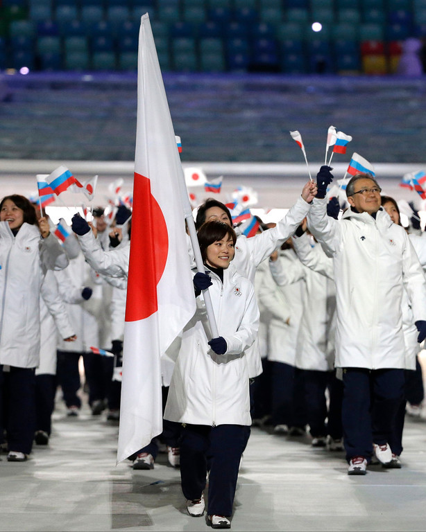 . Ayumi Ogasawara of Japan carries the national flag as she leads the team during the opening ceremony of the 2014 Winter Olympics in Sochi, Russia, Friday, Feb. 7, 2014. (AP Photo/Mark Humphrey)