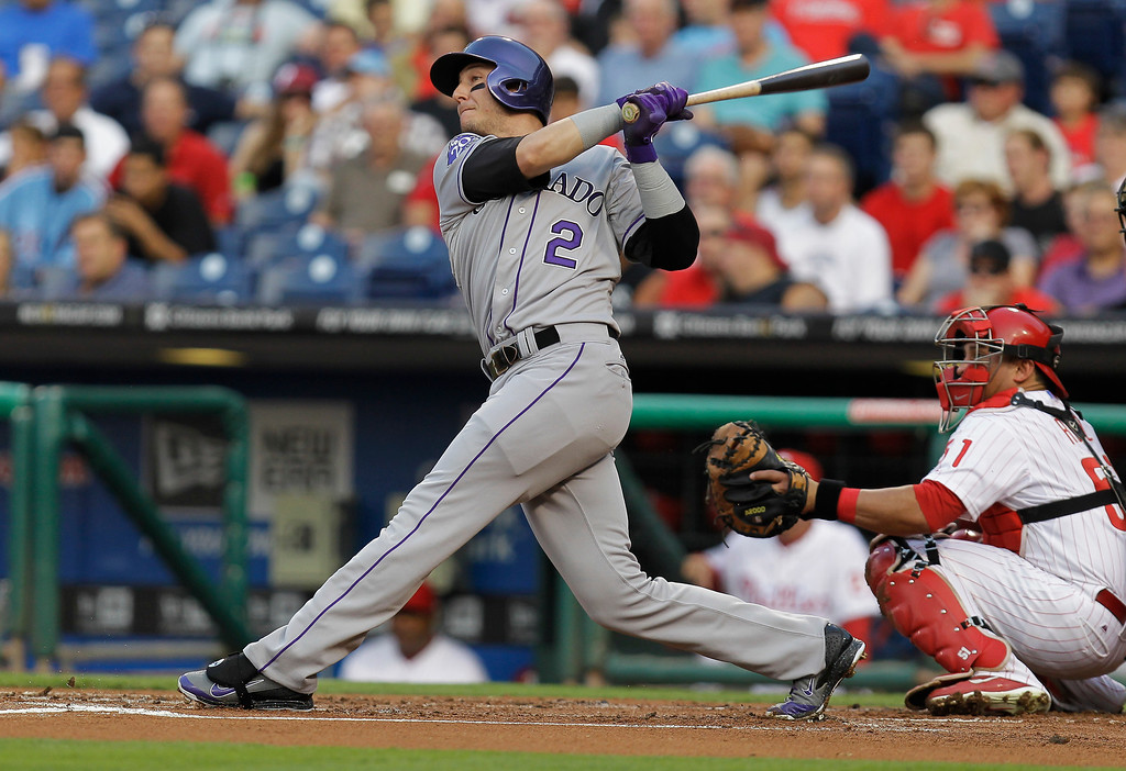 . Colorado Rockies\' Troy Tulowitzki follows through on a home run off Philadelphia Phillies pitcher Tyler Cloyd in the first inning in a baseball game, Tuesday, Aug. 20, 2013, in Philadelphia. (AP Photo/Laurence Kesterson)
