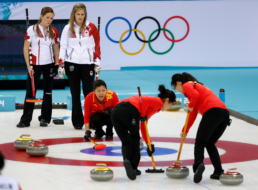 . Chinaís Liu Yin, center, shouts instructions from the house as Yue Qingshuang, second from left, and Zhou Yan, sweep ahead of the rock in a game against Canada during women\'s curling competition at the 2014 Winter Olympics, Monday, Feb. 10, 2014, in Sochi, Russia. Canada\'s Kaitlyn Lawes, left, and Jennifer Jones look on. (AP Photo/Robert F. Bukaty)