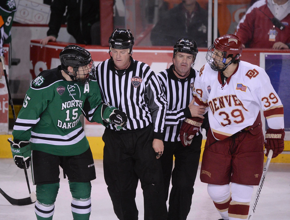 . DENVER, CO. - JANUARY 24:  North Dakota wing Michael Parks (15) kept talking to Denver wing Grant Arnold (39) as they were escorted to the penalty boxes in the third period. The University of Denver hockey team hosted North Dakota at Magness Arena Friday night, January 24, 2014. Photo By Karl Gehring/The Denver Post