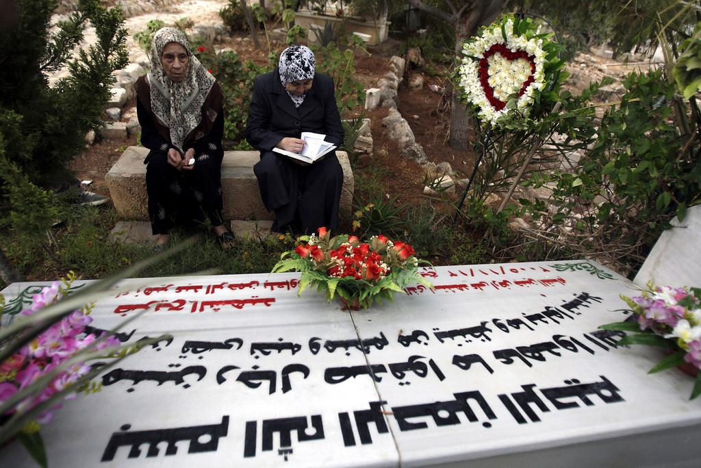 . Palestinian women read from the Quran, Islam\'s holy book, as they sit at the grave of a relative, as a part of tradition during the first day of Eid al-Fitr which marks the end of the Muslim fasting month of Ramadan in the West Bank city of Jenin, Thursday, Aug, 8, 2013. (AP Photo/Mohammed Ballas)