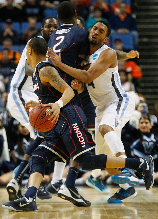. Villanova\'s Darrun Hilliard II (4) runs into a pick set by Connecticut\'s DeAndre Daniels (2) as he chases Shabazz Napier during the first half of a third-round game in the NCAA men\'s college basketball tournament in Buffalo, N.Y., Saturday, March 22, 2014. (AP Photo/Bill Wippert)